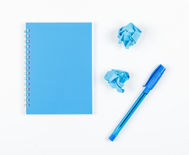 Note taking concept with crushed paper, pen, notebook on white background top view. horizontal image