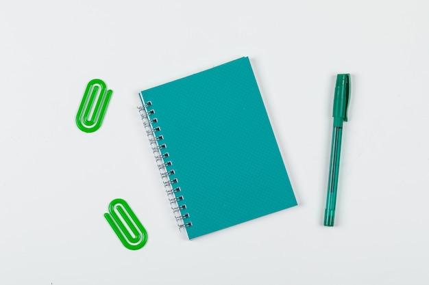 Примечание принимая концепцию с тетрадью, ручкой, бумажными зажимами на белом взгляд сверху предпосылки. горизонтальное изображение