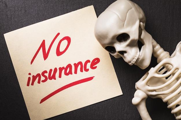 Примечание с текстом и концепцией человеческого скелета отсутствия страховки