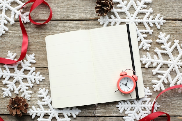 Notebook and alarm clock on snowflakes