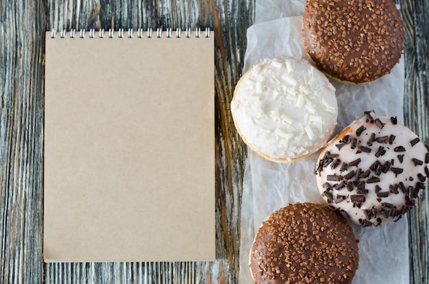 Блокнот и ассорти пончики с шоколадной глазурью на деревянной поверхности