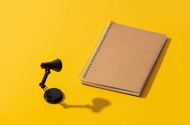 Ноутбук и черная маленькая лампа на желтой поверхности