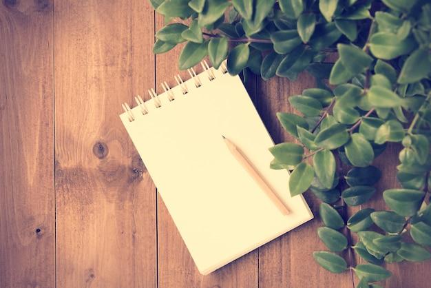 ノートと木製のテーブルに茶色の鉛筆