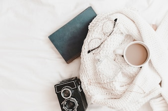 Notebook and camera near sweater with things on bedsheet