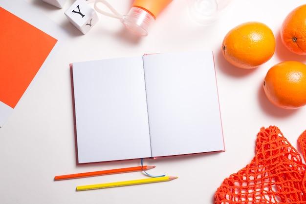 ノートブックとテーブルの上の新鮮なオレンジ、フラットレイ