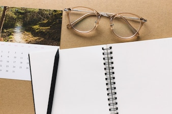 Notebook and glasses near calendar