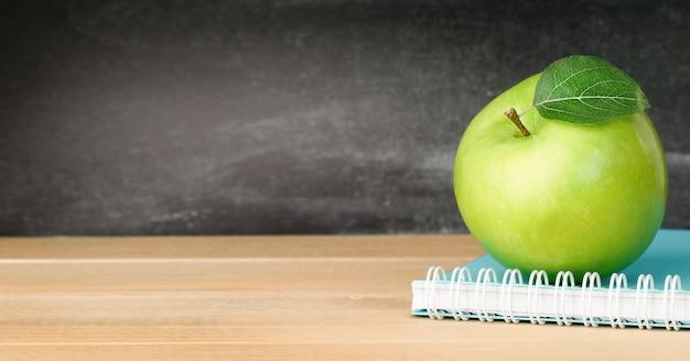 칠판의 배경에 대해 테이블에 노트북과 녹색 사과