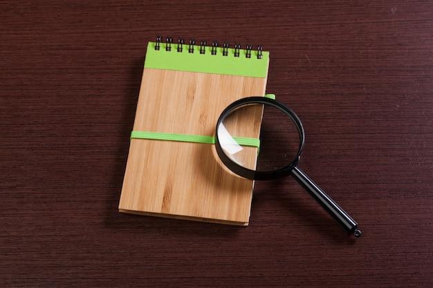 Блокнот и лупа на деревянной поверхности