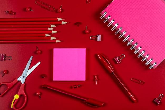 Блокнот и бумага розового цвета с местом для текста, канцелярские принадлежности для школы и офиса красного цвета лежат на красном фоне.