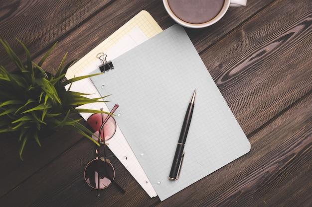 ポットトップビューで木製のテーブルコーヒーカップの花のノートとペン