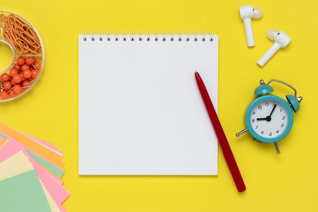 黄色の背景にノートとペン。メモ帳、白いヘッドホン、目覚まし時計、クリップ、職場のカラフルなステッカー。