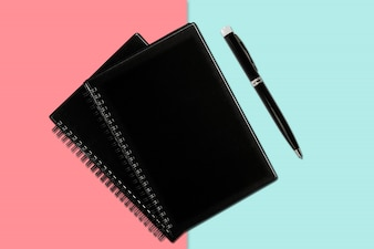 Notebook and pen on colored background