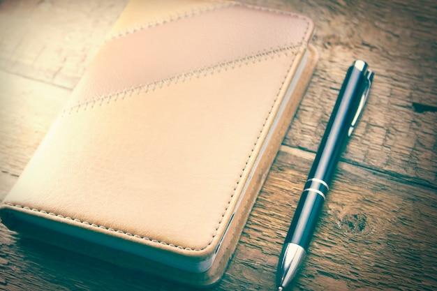 ノートブックと木製の背景の上のペン