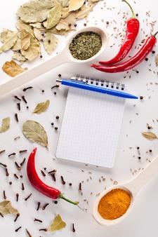 Блокнот и ручка для написания рецептов вокруг острого красного перца со специями на белом фоне