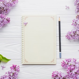 Notebook and pencil near lilac