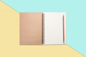 Notebook and pencil on colored background