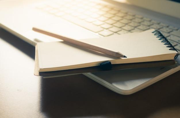 아침 빛, 빈티지 색상 효과와 노트북 키보드에 노트와 연필 장소
