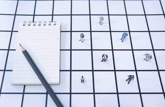 ビジネスマンのミニチュアチームがいるノートと鉛筆は、隔離中に自宅や社外から離れて働きます。自己分離、在宅勤務、社会的距離、コロナウイルス、covid-19コンセプト。