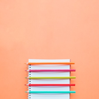 Notebook and pencils on peach background