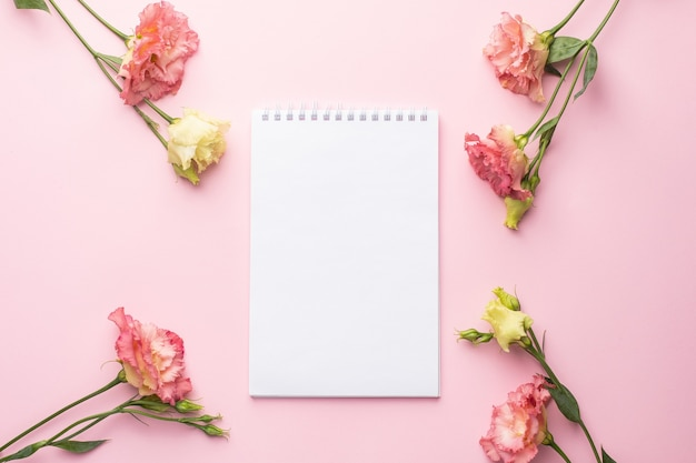 파스텔 배경에 노트북과 핑크 꽃 꽃다발