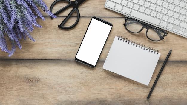 Блокнот и смартфон рядом с цветами лаванды и клавиатурой
