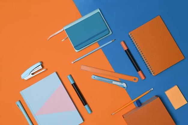 青とオレンジのツートンカラーの背景にノートブックとステーショナリー。