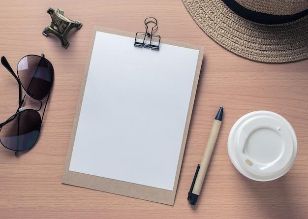 ノートブックと旅行のオブジェクトは、木製のテーブルの背景にヴィンテージフィルター