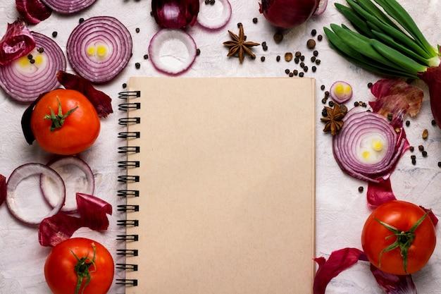 Тетрадь и овощи на светлой предпосылке.