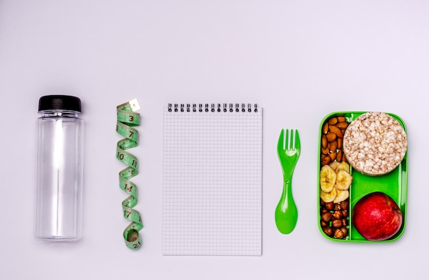 Notebook, apple, nuts, banana chips, bread rolls in a food container
