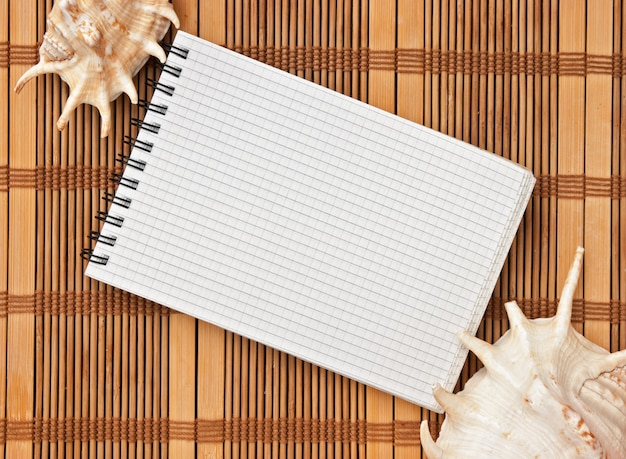 Notebook on the background of mats and sea shells