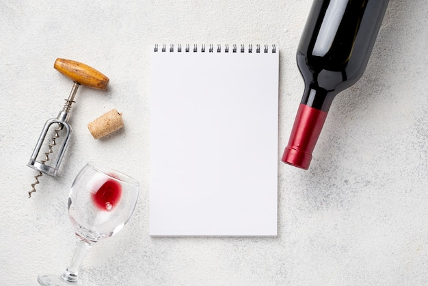 Notebook beside wine bottle and glasses