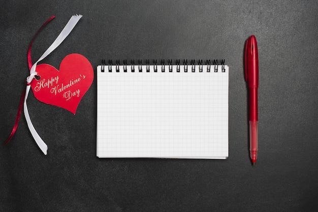펜과 인사말 카드 사이의 노트북