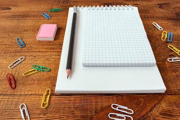 Пустой блокнот с карандашом, ластиком и скрепками.