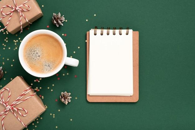 노트북 빈 종이 모형, 황금색 별 색종이 조각, 선물 상자, 녹색 배경에 머그 커피