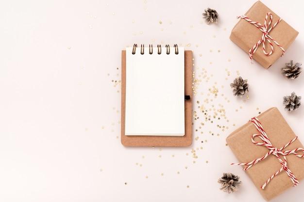 노트북 빈 종이 모형, 황금색 별 색종이 조각, 베이지색 배경에 선물 상자. 평평한 평지, 평면도, 복사 공간, 미니멀리스트. 크리스마스 새 해 구성입니다.