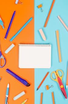 Блокнот, синие и сиреневые школьные принадлежности на фоне