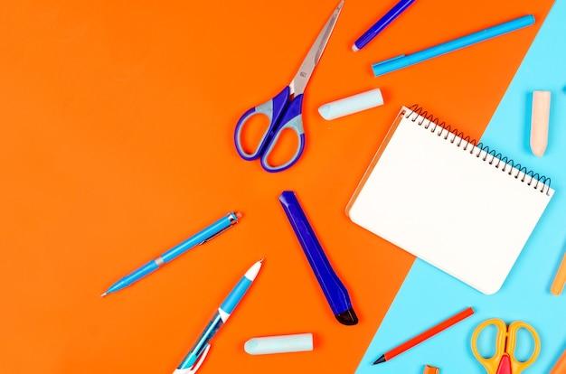 ノートブック、青とオレンジの学用品、青の背景。教育の概念。コピースペースを使用して上から表示します。モックアップ、フラットレイ
