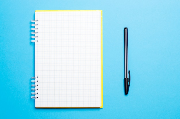 Notebook on a blue background with pens