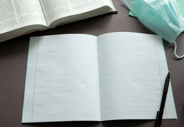 ノート、本、テーブルの上のペン。通信教育。