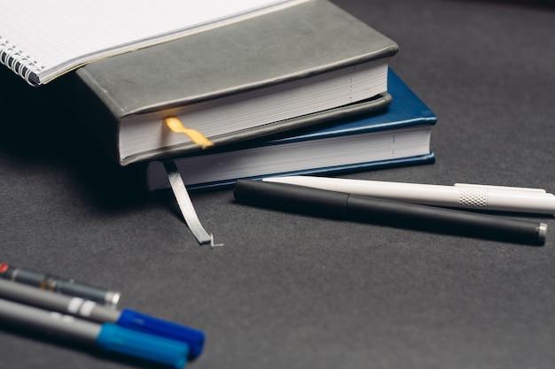 Ноутбук книги ручки документы на рабочем месте офис серый фон