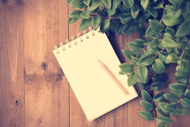 Notebook and brown pencil on wooden table