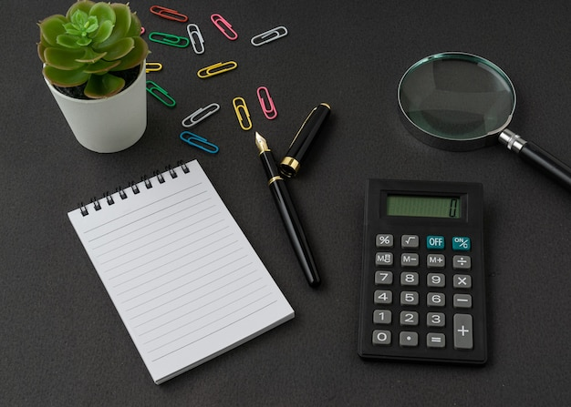 A notebook, calculator, magnifying glass and pen on black surface with a copy space. business and finance concept.