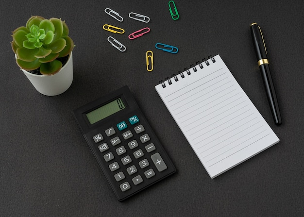 A notebook, calculator and pen on black surface with a copy space. business and finance concept.