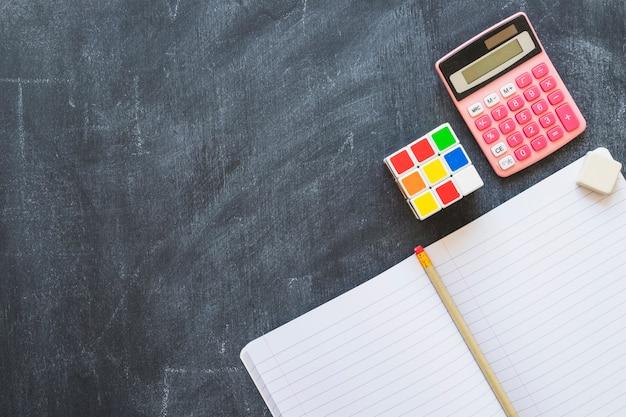 Notebook calculator and rubiks cube on blackboard