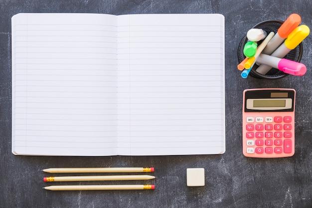 Notebook calculator and stationery on blackboard
