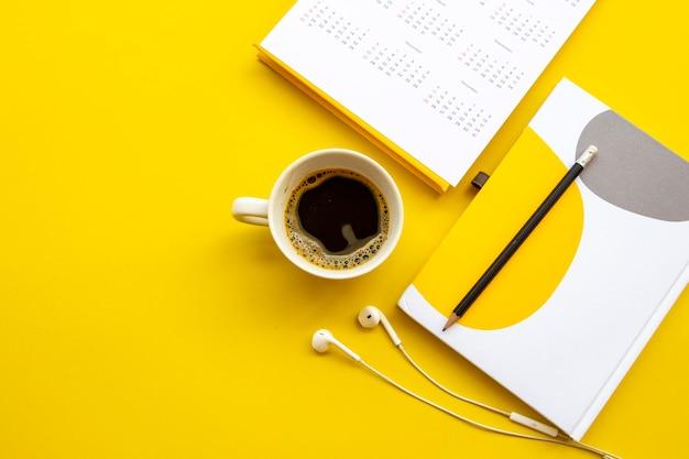 ノートブックカレンダーと背景黄色のコーヒーの配置
