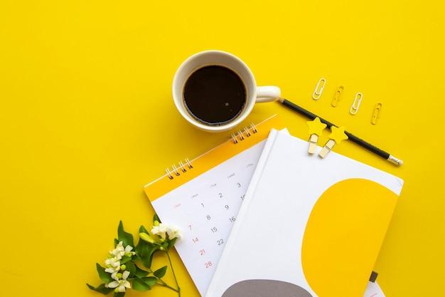 背景黄色の作業のためのノートブックcarlendar
