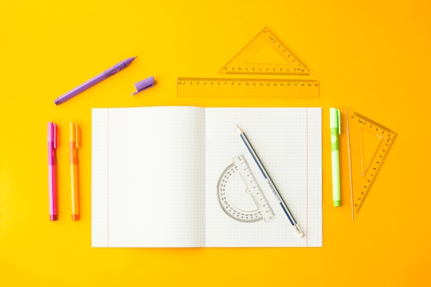 Notebook in a cell among pens, pencils and rulers on a yellow background