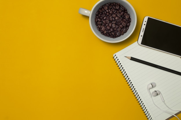 Notebook and coffee bean on the color background
