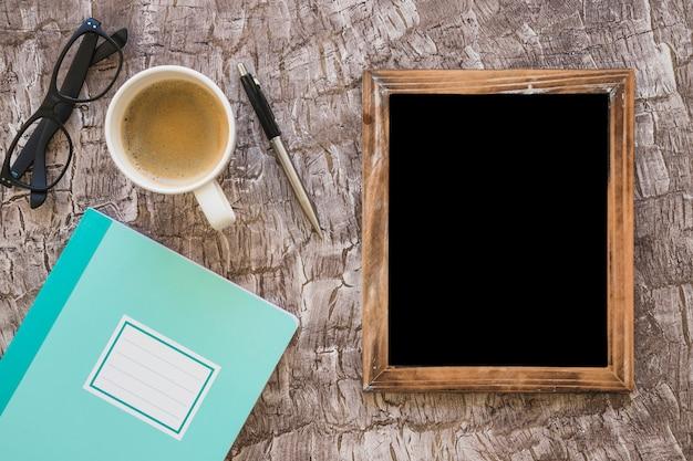 Notebook; coffee cup; eyeglasses; pen and blank blackboard on textured backdrop